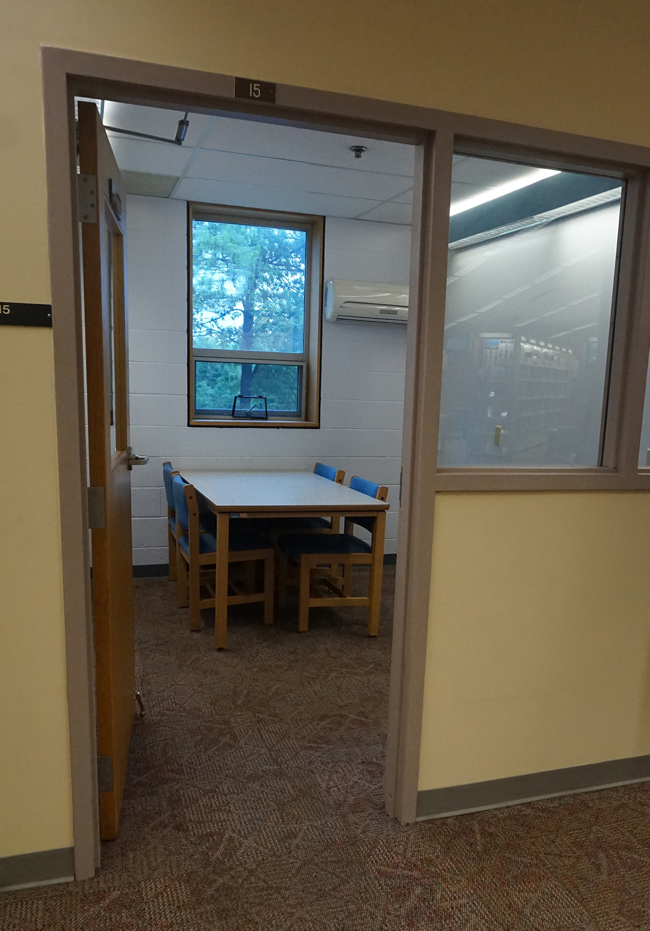 Entrance into a small study room with four chairs and a table