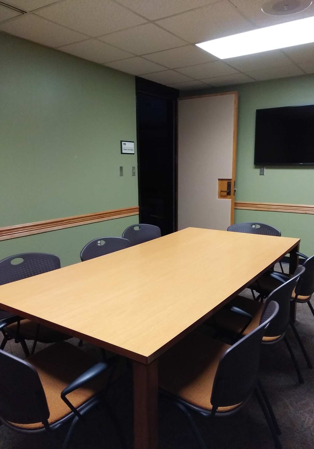 Small room with rectangular table and multiple chairs