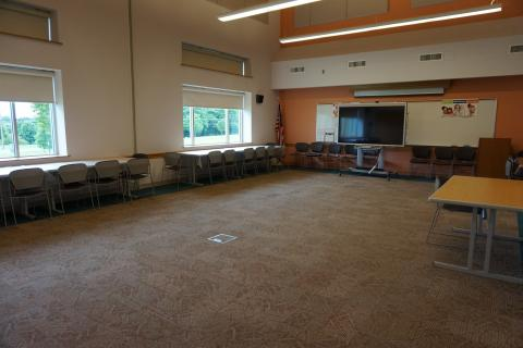 Finksburg large meeting room with open room setup and tables and chairs on side