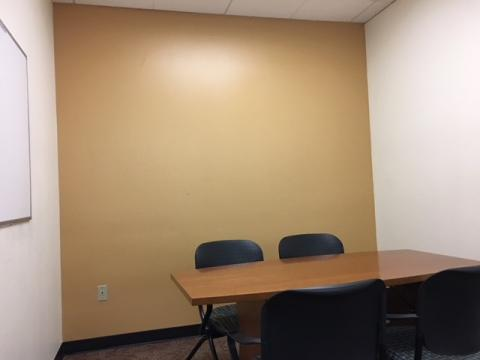 Small meeting room with table, white board mounted on wall, and seating for four