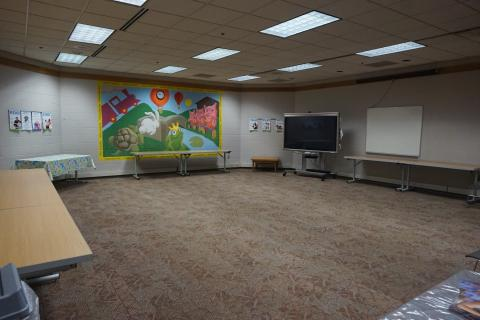 Large open room with carpet, tables lining the walls, and a colorful mural
