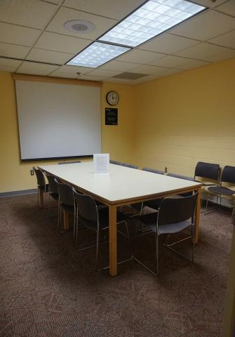 Rectangular table with chairs, white screen at front