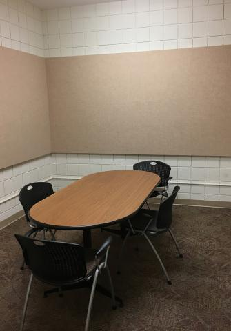 Small room with a rectangular table with four chairs placed around the table